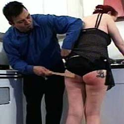 A young man reddens the buns of a young girl when he uses a stick to whale away at her.