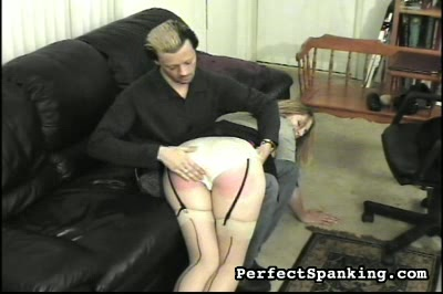 Acup cutie spank and paddled by man and woman. Her black garters and seamed stockings just add to the eroticism of this scene. Off the knee, on her feet, commanded to remove her top.